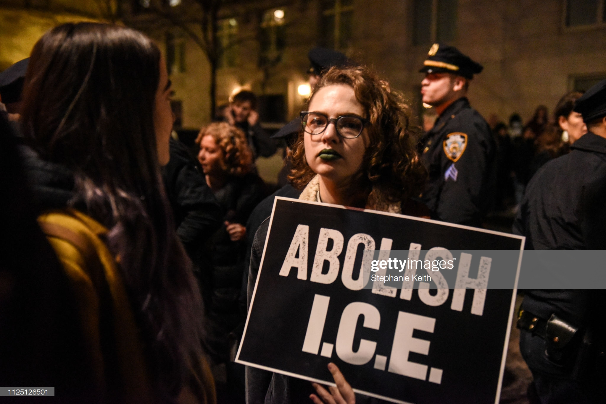 """NEW YORK, NY - FEBRUARY 15: People hold signs that read """"Abolish I.C.E."""" in front of Trump International Hotel on February 15, 2019 in New York City. The group is protesting U.S. President Donald Trump's declaration of a National Emergency in order to build his proposed border wall. (Photo by Stephanie Keith/Getty Images)"""